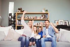 与被举的胳膊的愉快的家庭,当看电视时 免版税库存图片