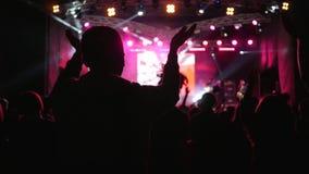 与被举的胳膊的跳舞青年时期获得在夜事件的明亮地被点燃的阶段背景的乐趣  影视素材