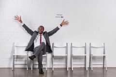 与被伸出的胳膊等待的微笑的非裔美国人的商人 库存图片