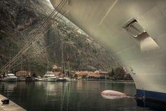 与被停泊的巡航船舶船的海洋海港在中世纪科托尔海湾在黑山在阴暗多雨秋天天 免版税图库摄影