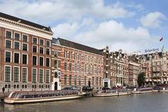 与被停泊的游览小船,阿姆斯特丹,荷兰的古老豪宅 免版税库存照片