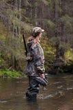 与被充塞的鸭子的妇女猎人在河 免版税库存图片