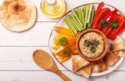 与被分类的新鲜蔬菜和皮塔饼面包的自创hummus 图库摄影