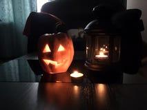 与被切开的眼睛的与一个蜡烛的南瓜和嘴里面在灯笼旁边的黑暗的背景-万圣夜的标志 免版税库存图片