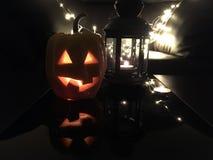 与被切开的眼睛的与一个蜡烛的南瓜和嘴里面在灯笼旁边的黑暗的背景-万圣夜的标志 库存照片