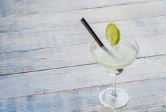 与被切的石灰的经典石灰玛格丽塔酒鸡尾酒在木背景 免版税库存照片
