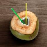 与被删去的心脏形状的新鲜的绿色年轻在木背景的椰子和秸杆 免版税图库摄影