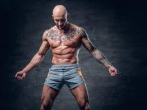 与被刺字的身体的被刮的顶头赤裸上身的肌肉男性 免版税图库摄影