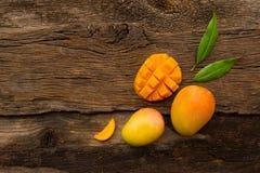 与被削减的切片的芒果在木背景的果子和叶子 免版税库存图片