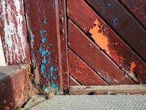 与被剥皮的油漆的老棕色木门 免版税库存图片