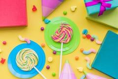 与被包裹的礼物、贺卡和甜点的生日概念在黄色背景顶视图 库存图片