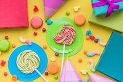 与被包裹的礼物、贺卡和甜点的生日概念在黄色背景顶视图 免版税库存照片