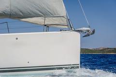 与被卷扬的前桅前方的帆和拷贝空间的风船弓在小船船身 图库摄影