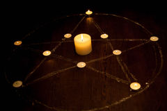 与被射击的蜡烛的神秘的五角星形在黑暗中,在木背景 免版税库存图片