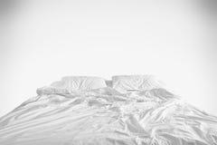 与被弄皱的床单、一条毯子和枕头的没有整理好的床在舒适醒在白色的早晨的鸭绒垫子睡眠以后 库存图片