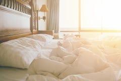 与被弄皱的床单和枕头的没有整理好的床在舒适醒早晨的鸭绒垫子睡眠以后 库存照片