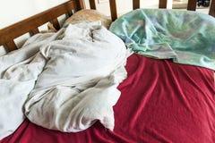 与被弄皱的红色和白色床单和药片的没有整理好的儿童床 图库摄影
