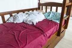 与被弄皱的红色和白色床单和药片的没有整理好的儿童床 免版税库存照片