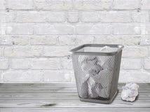与被弄皱的纸的一个垃圾箱在地板上站立对一个白色砖墙 库存照片