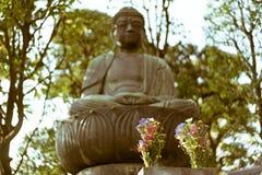 与被弄脏的菩萨雕象的日本花在背景中 免版税库存图片