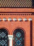 与被成拱形的被弄脏的窗口的红砖门面 库存图片