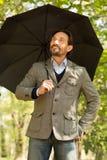 与被打开的伞的商人 图库摄影