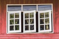 与被打开的窗帘的木房子窗口 免版税库存照片