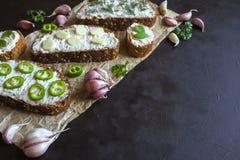 与被抹上的大蒜奶油的面包在黑桌上 开胃菜用蒜酱油 免版税库存图片