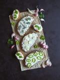 与被抹上的大蒜奶油的面包在黑桌上 开胃菜用蒜酱油 库存照片