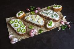 与被抹上的大蒜奶油的面包在黑桌上 开胃菜用蒜酱油 免版税库存照片