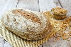 与被拼写的五谷的被拼写的面包在木桌上 免版税库存图片