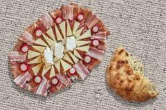 与被撕毁的皮塔小面包干大面包一半集合的开胃菜美味盘在粗糙的被漂白的黄麻帆布难看的东西背景 免版税库存图片