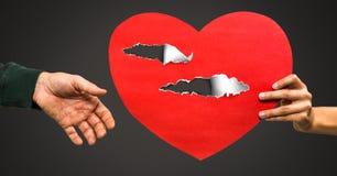 与被撕毁的纸的夫妇藏品疼的爱心脏 免版税库存照片