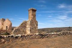 与被放弃的房子和烟囱的干旱的风景在前景 免版税库存照片