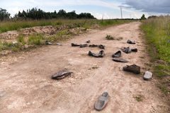 与被放弃的鞋子的老农村路 免版税库存图片