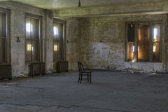与被日光照射了窗口的空的椅子 库存图片