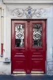 与被构筑的木盘区的古色古香的红色门和在老大厦门窗口的华丽栅格在巴黎法国 葡萄酒门道入口 免版税库存图片