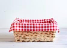 与被检查的红色野餐布料的空的秸杆篮子 免版税图库摄影