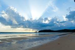 与被点燃的云彩的热带海滩日落天空 图库摄影