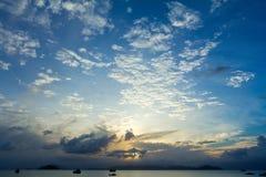 与被点燃的云彩的热带海滩日落天空 库存照片