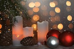 与被点燃的蜡烛、锥体和欢乐球的静物画在一本圣诞树和诗歌选旁边在背景中 库存图片