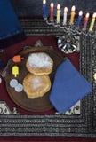 与被点燃的蜡烛的光明节Menorah,礼物、Dreidel和果冻填装 免版税库存照片