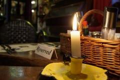 与被点燃的蜡烛的餐馆后备的桌标志 库存图片
