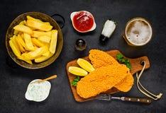 与被烘烤的鱼和啤酒的炸薯条 免版税库存照片