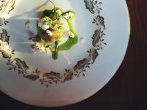 与被粉碎的乳清干酪、绿色荨麻纯汁浓汤和microgreens的乳清干酪gnudi 库存照片