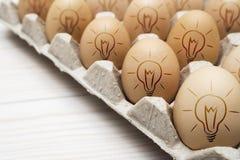 与被绘的电灯泡的许多鸡蛋在纸板容器 免版税库存图片