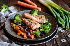 与被蒸的菜的油煎的三文鱼 图库摄影