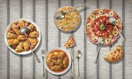 与被装饰的开胃菜盘和奥利维尔沙拉的泡菜卷在纸羊皮纸位置字块服务 库存图片