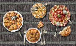 与被装饰的开胃菜盘和奥利维尔沙拉的泡菜卷在纸羊皮纸位置字块服务 免版税图库摄影