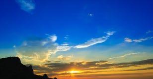 与被覆盖的橙色天空和山剪影的美好的日落 免版税库存照片